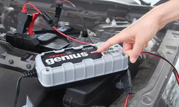 The mode bottom on the NOCO Genius G7200 Battery Charger and Maintainer charging car battery is being pressed.